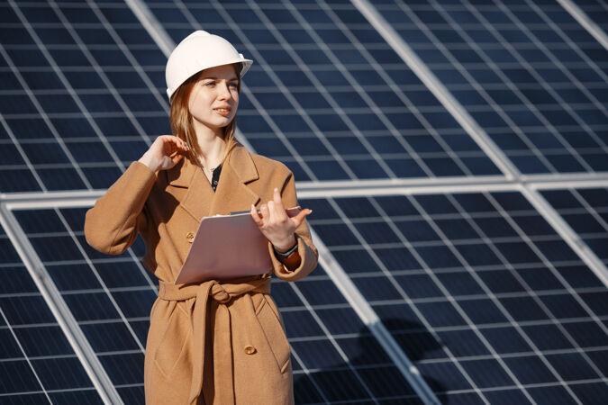 在太阳能发电厂检查设备的女商人使用平板电脑清单 在太阳能发电厂户外工作的女商人