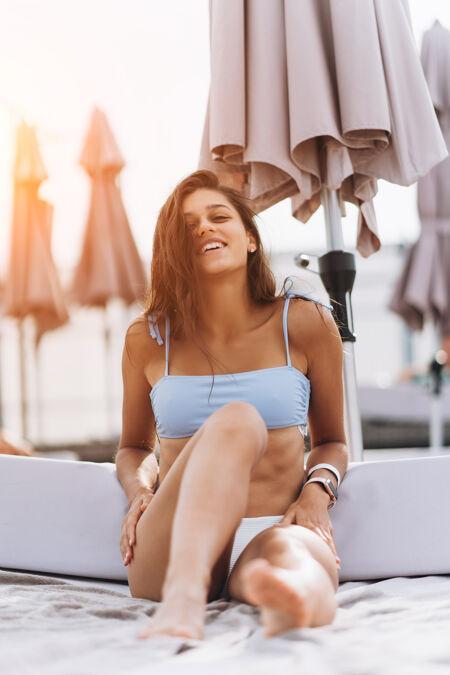 穿着比基尼的漂亮年轻女子在泳池边休息