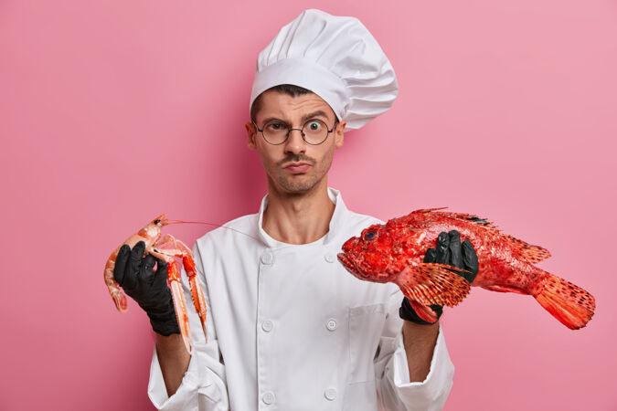 年轻帅气的厨师手拿生小龙虾