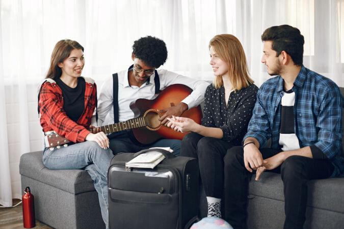一群形形色色的朋友聚在家里一个人一边弹吉他一边唱歌