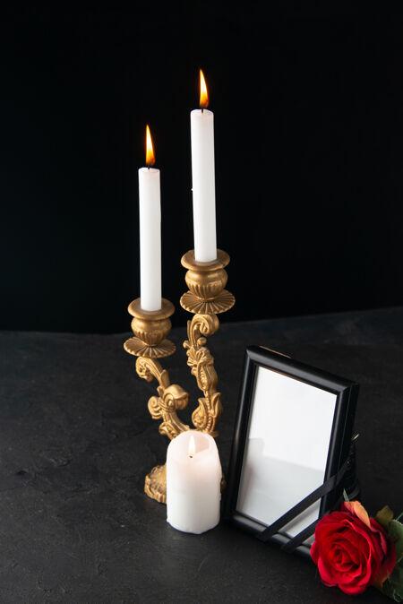 前视图燃烧蜡烛与图片框在黑暗的表面