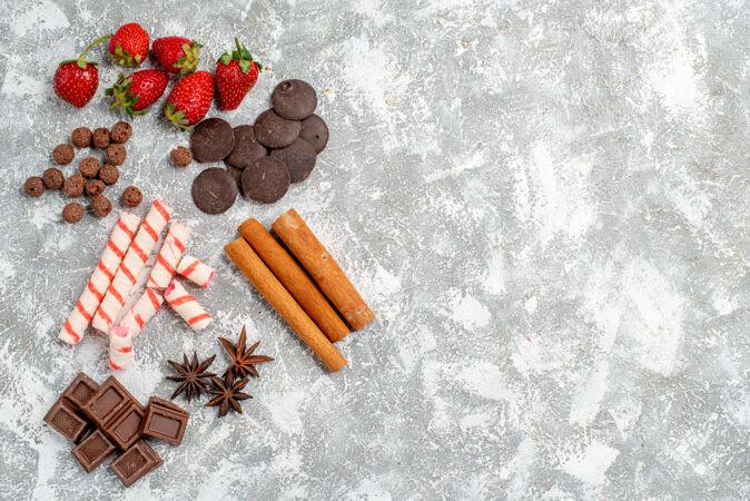顶视图草莓巧克力糖果谷类食品肉桂茴香种子在灰白色桌子的左侧有自由空间