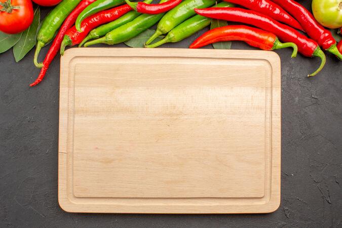 顶视图:红 绿辣椒 西红柿 月桂叶和黑土地上的砧板