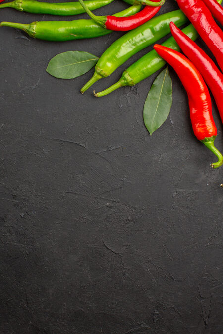顶视图红色和绿色的辣椒湾叶在顶部的黑色桌子与自由空间