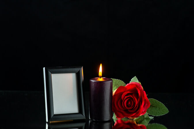 在黑暗的表面上有红玫瑰和画框的黑暗蜡烛的正面视图