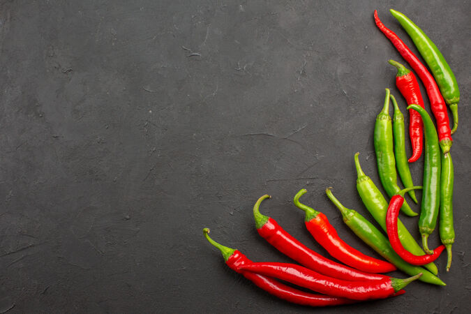 顶视图红色和绿色的辣椒在黑色桌子的右下角与自由空间