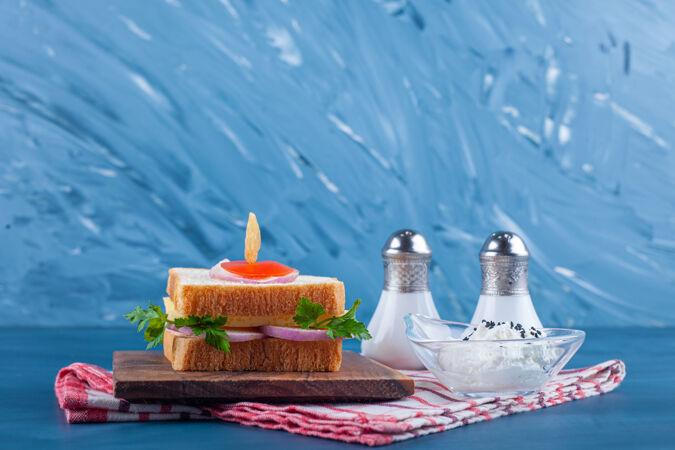 三明治放在一块木板上 旁边放着盐和一碗奶酪 放在茶巾上 放在蓝色的桌子上