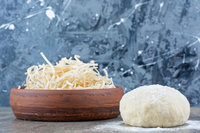 塞西尔奶酪放在面团旁边的碗里 放在大理石桌上