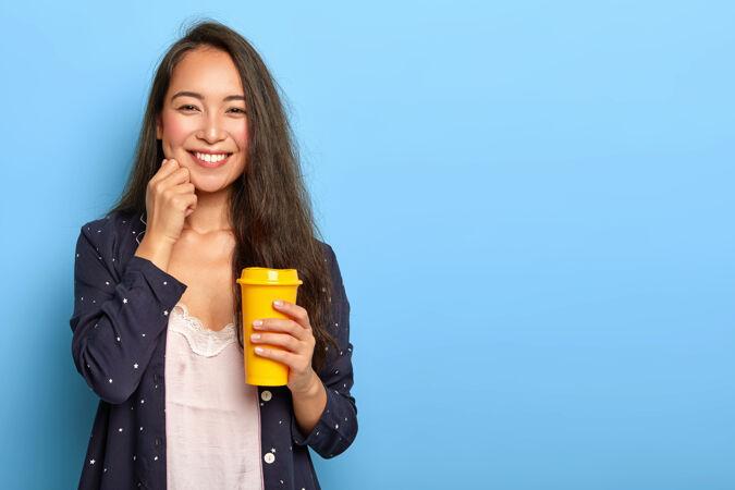 容貌讨人喜欢的东方黑发女青年 轻抚脸颊 笑容可掬 身穿睡衣睡衣 端着一杯黄色外卖咖啡
