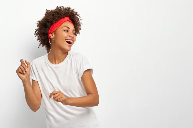 快乐积极的女人高兴地看着远方 随着音乐的节奏跳舞 把头转过去 穿着休闲服
