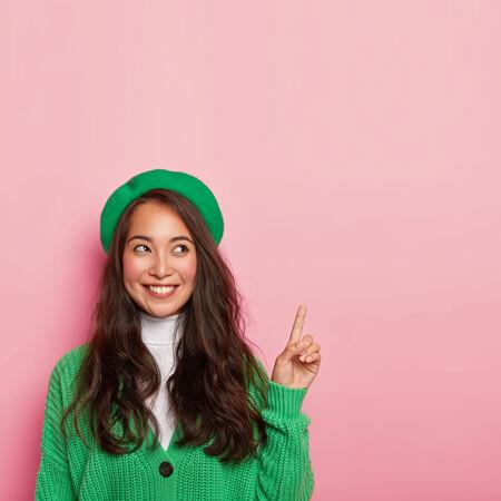帅气的亚洲女士戴着绿色贝雷帽和针织套头衫 手指上方 表情开朗