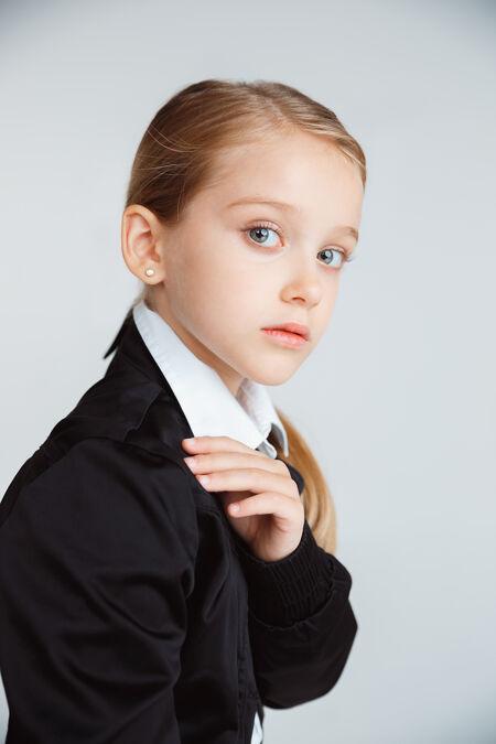 在漫长的暑假后准备上学的女孩回到学校穿着校服的白人小女模在白墙上摆姿势童年 教育 假期的概念