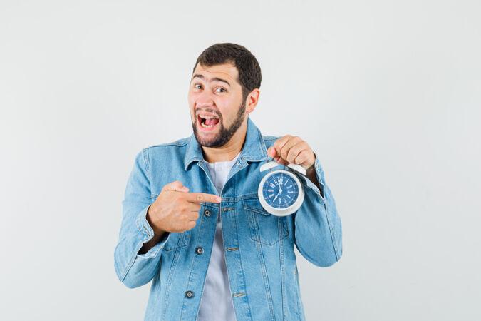 复古风格的男士夹克衫 t恤衫指着时钟 看起来很高兴 正面视图