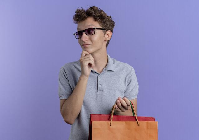 一个戴着黑眼镜 穿着灰色马球衫 手拿纸袋的年轻人站在蓝色的墙上 一边看一边 一边用下巴思考着