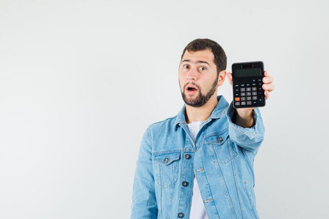 复古风格的男子展示计算器在夹克衫 t恤衫和期待惊喜 前视图文本空间