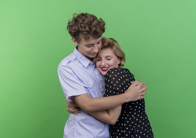 年轻美丽的夫妇站在一起幸福相爱拥抱站在绿色的墙