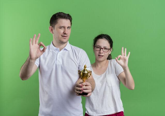 年轻的运动情侣站在一起拿着奖杯微笑着表示ok标志站在绿色的墙上