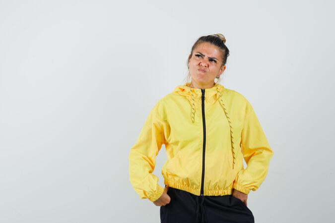 穿着运动服的女人摆姿势 一边思考 一边犹豫不决地看着前方