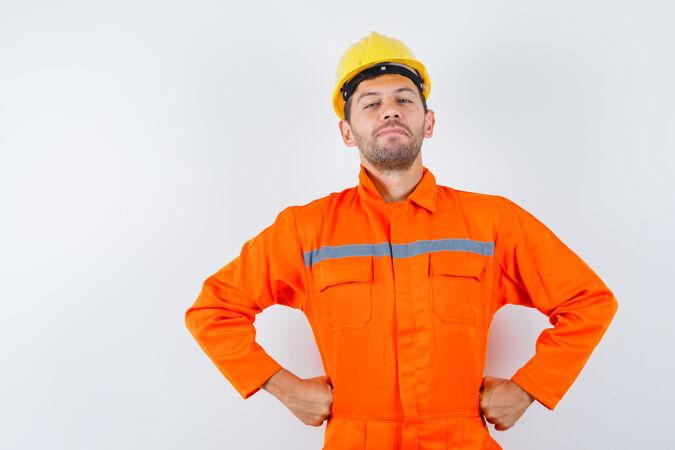 穿着制服的建筑工人 手举头盔放在腰上 看上去很自信 前视图