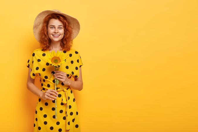 红发女人穿着黄色的波尔卡裙 戴着草帽