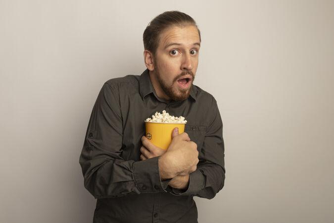 穿着灰色衬衫的年轻帅哥拿着装满爆米花的桶忧心忡忡