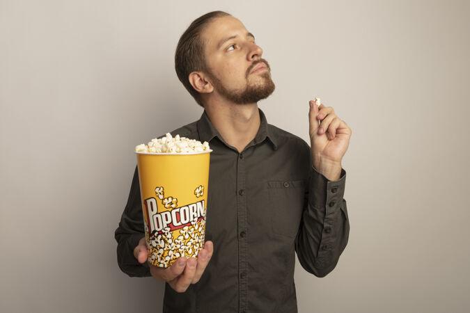一个穿着灰色衬衫的年轻帅哥 手里拿着一桶爆米花 严肃地看着一边