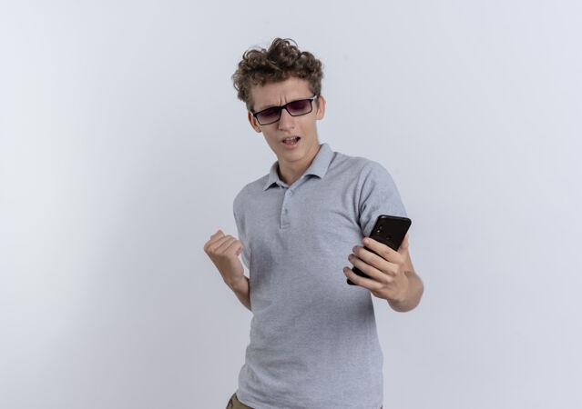 身穿灰色马球衫的年轻人看着智能手机屏幕握紧拳头 为自己站在白墙上的成功而欢欣鼓舞
