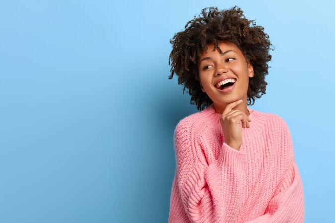 一个有魅力的女人 穿着粉色毛衣摆着非洲裔的姿势