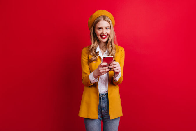 迷人的法国女孩在红墙上打电话穿着黄色夹克拿着智能手机的金发女人