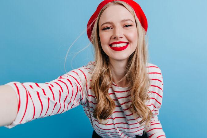 戴贝雷帽的金发女孩兴奋地在蓝色的墙上自拍穿着条纹衬衫的无忧无虑的年轻女子
