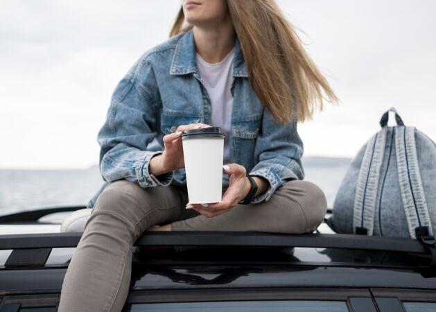 拿着一杯模拟咖啡的旅行者