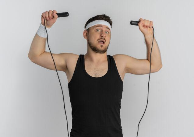 戴着头巾拿着跳绳的年轻健身男子要站在白色背景上跳