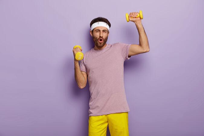 有趣的男人有乐趣 练习哑铃 穿着运动服 为健康的生活方式而努力 早上有规律的训练
