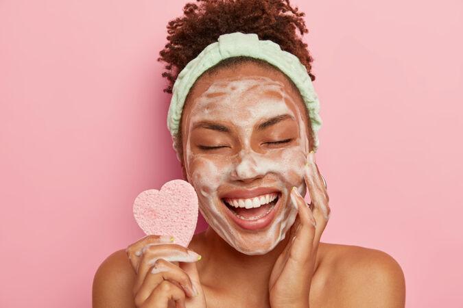 轻松愉悦的黑皮肤女模特用肥皂泡洗脸 享受娇生惯养 闭上眼睛不去享受 拿着化妆海绵 关心身体 赤裸着站在室内