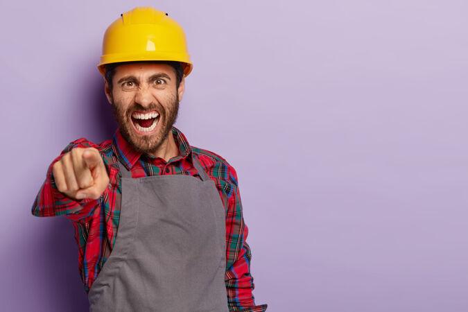 恼怒的工头指着照片 大喊大叫 怒吼科莱格 戴着黄色头盔 衬衫和围裙恼怒的建筑工人解决了工作中的问题