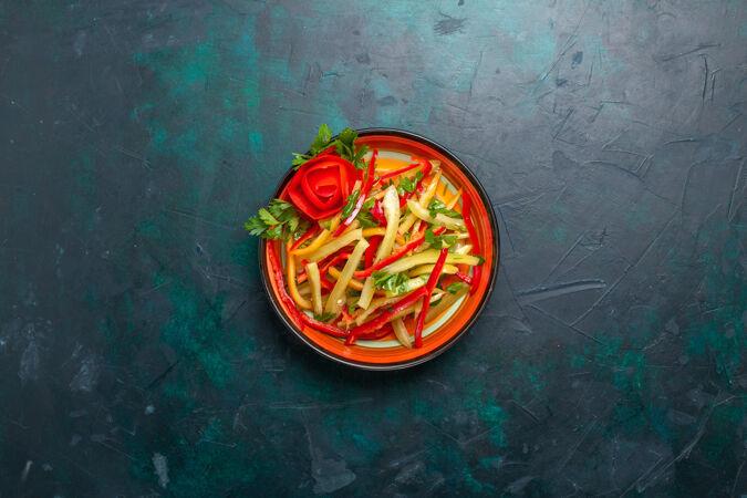 顶视图切碎的甜椒不同颜色的蔬菜沙拉在深蓝色背景的盘子里
