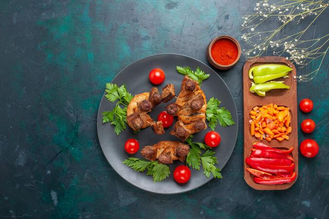 俯视图:蓝色背景的盘子里放着蔬菜和樱桃西红柿的肉片