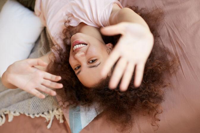 年轻开朗的非洲裔美国妇女在家里享受阳光明媚的日子 在家休息 躺在床上 面带微笑
