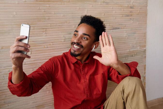 室内肖像的年轻短发胡须男性皮肤黝黑 举手打招呼 微笑愉快 同时进行视频通话 孤立在家庭内部