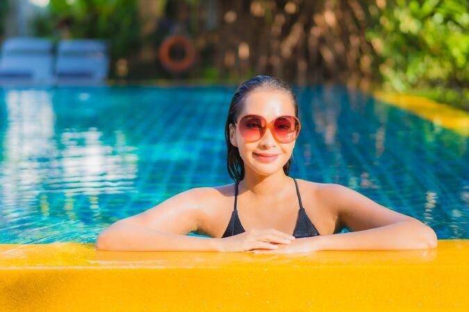 肖像美丽的亚洲年轻女子放松微笑休闲围绕室外游泳池近海