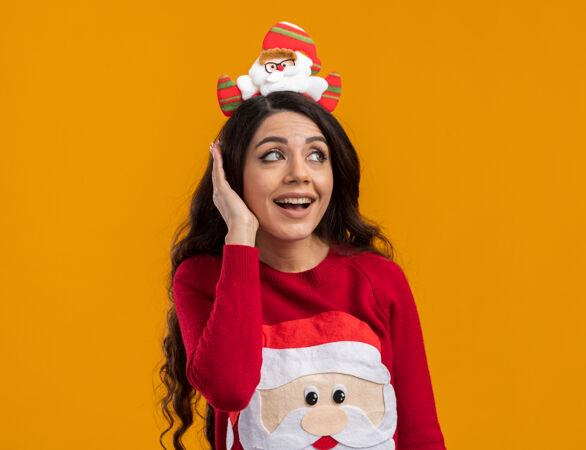 令人印象深刻的年轻漂亮女孩戴着圣诞老人的头带和毛衣看着一边保持手在头上橙色背景隔离