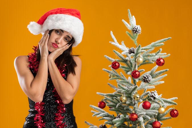 悲伤的歪头年轻漂亮的女孩戴着圣诞帽 脖子上戴着花环 站在圣诞树旁 把双手放在脸颊上 隔离在橙色的墙上