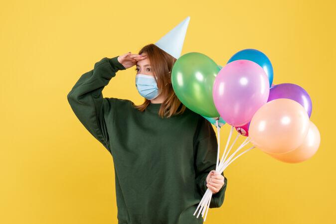 正面图:手持彩色气球的年轻女性