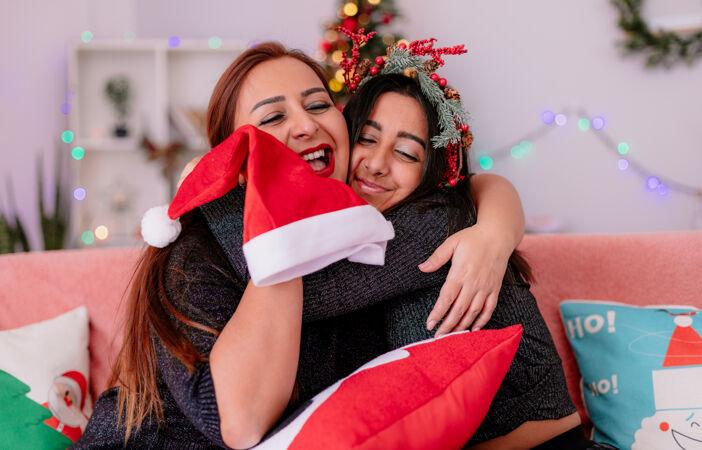 可爱的女儿和妈妈坐在沙发上互相拥抱 在家里享受圣诞节时光