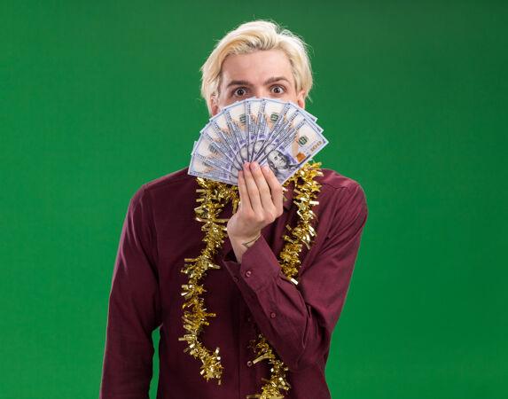 令人印象深刻的年轻金发男子戴着眼镜 脖子上戴着金箔花环 从后面拿着钱 隔离在绿色墙壁上 留着复印空间