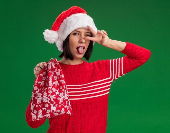 顽皮的小女孩戴着圣诞帽拿着圣诞礼物袋 舌头和v字符号靠近绿色墙上的眼睛