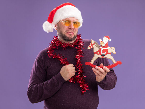 皱眉的中年男子戴着圣诞老人帽 脖子上戴着金箔花环 戴着眼镜 把圣诞老人抱在紫色墙上的摇马雕像上