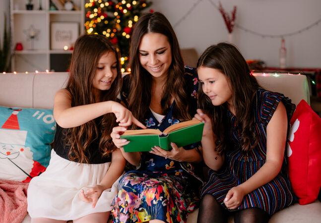 两个妹妹和年幼的妈妈在家过圣诞节的时候坐在客厅的沙发上微笑着妈妈看书给女儿小女儿笑着指着书