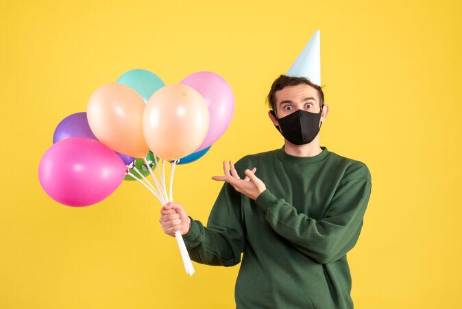 正面图:戴着派对帽和黑色面具的年轻人指着黄色的气球