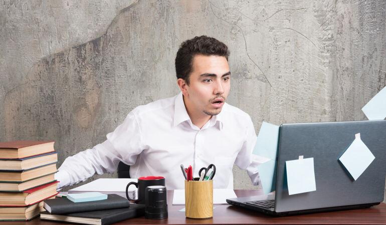 商人在办公桌上看着笔记本电脑 表情很震惊